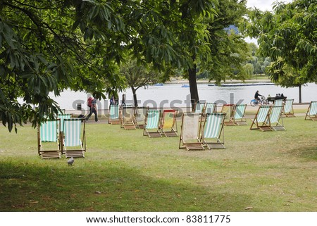 Deckchairs for hire by The Serpentine boating lake in Hyde Park. Westminster. London. England. - stock photo