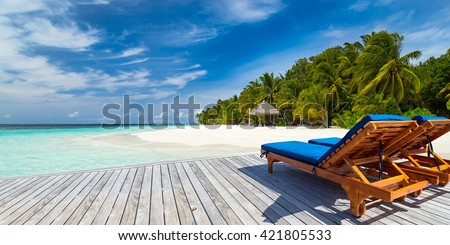 deckchairs on jetty in front of tropical island - stock photo