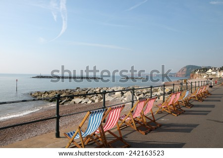 Deckchairs on seafront at Sidmouth in Devon - stock photo