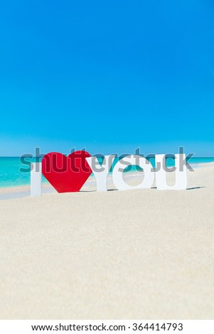 Declaration of I love you words with red heart at beach against waves and blue summer sky, St.Valentines day traveling or greeting card concept - stock photo