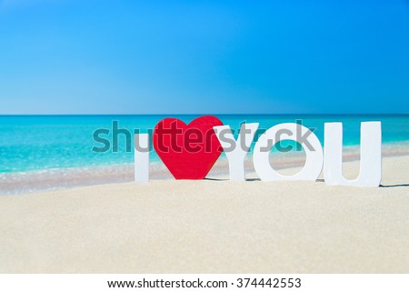Declaration of words I love you with red heart at sea sandy beach against waves and blue summer sky, Saint Valentines day travelling or greeting card concept - stock photo