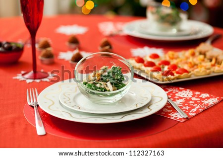 Decorated Christmas dining table with delicious salad (spinach, pear, blue cheese and pine tree nuts) - stock photo