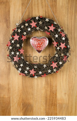 Decorated christmas door wreath with gingham birch stars and printed tin heart brown twigs on sapele wood background, copy space - stock photo