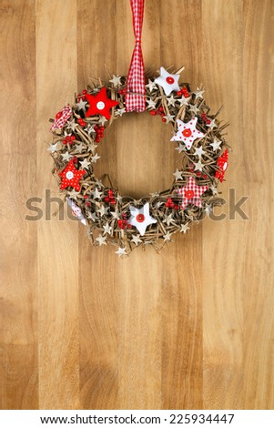 Decorated christmas door wreath with red and white pillow stars brown twigs gingham and polka dot on sapele wood background, copy space - stock photo