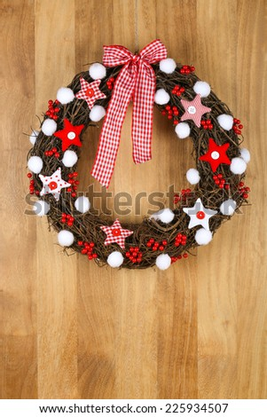 Decorated christmas door wreath with red and white pillow stars with gingham bow brown twigs gingham and polka dot on sapele wood background, copy space - stock photo