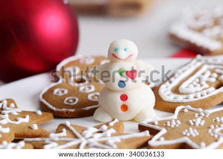 Decorated christmas sugar snowman and gingerbread cookies and edcorations on the table. - stock photo