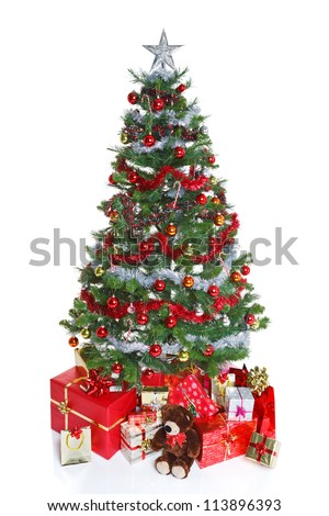 Decorated Christmas tree with baubles and tinsel surrounded by gift wrapped presents and a teddy bear, isolated on a white background. The teddy is generic, not a brand name bear - stock photo