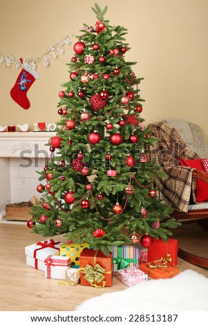 Decorated Christmas tree with gifts in room closeup - stock photo