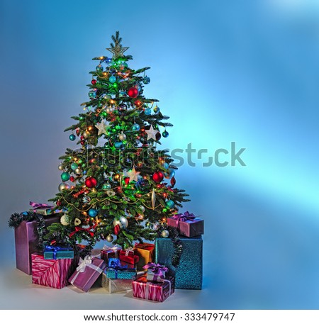 decorated Christmas tree with gifts on blue background - stock photo
