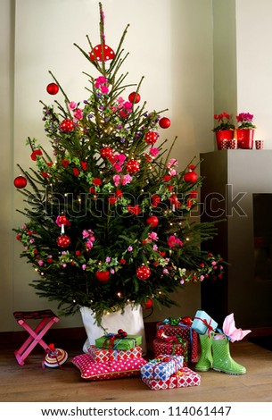 Decorated christmas tree with presents prepared on the floor - stock photo