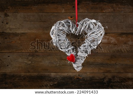 Decorated christmas wreath with gingham ribbon and red heart on old wooden rustic background, copy space - stock photo