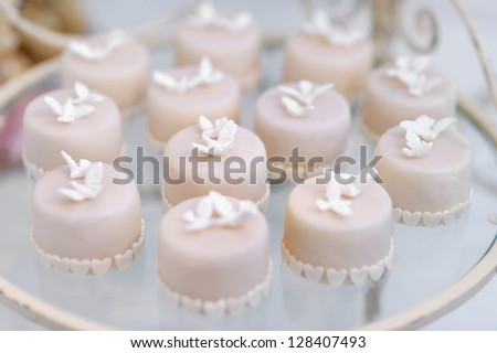 Decorated colorful cupcakes on a glass plate - stock photo