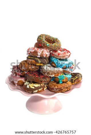 Decorated colorfull donuts with sweets on a pile isolated over white - stock photo