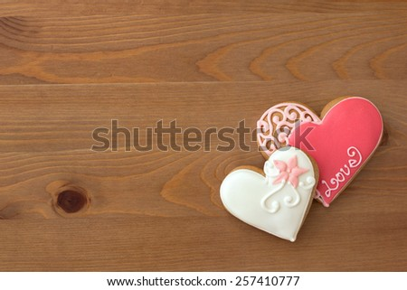Decorated cookies in the shape of heart on wooden table - stock photo