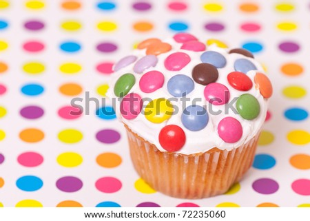 decorated cup cake on spotty background - stock photo
