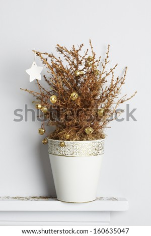 Decorated dead christmas pine tree on mantle piece. Unhappy xmas concept - stock photo