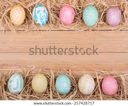 Decorated Easter eggs forming a border on a wood background - stock photo