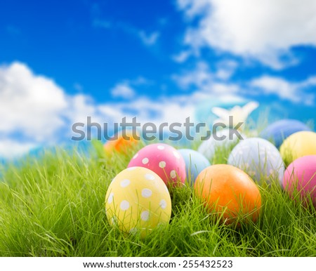 Decorated easter eggs in grass on sky background - stock photo