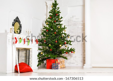 Decorated fir tree and gift boxes near fireplace in living room - stock photo