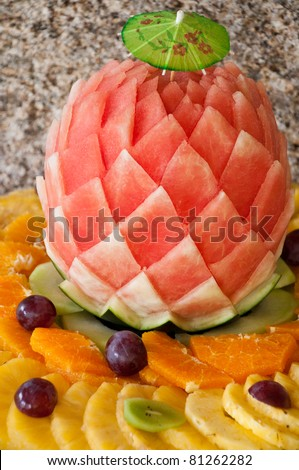 decorated fruit table setting with watermelon, grapes, orange and pineapple slices - stock photo