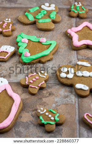 Decorated Gingerbread Christmas cookies on a tile counter top. - stock photo