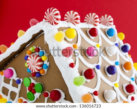 Decorated gingerbread house on red background. - stock photo