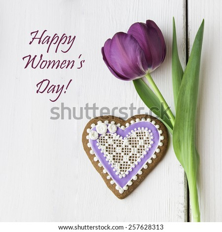 Decorated heart shaped cookie and tulip flower for Women's day. - stock photo