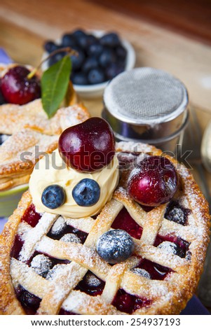 Decorated homemade shortcrust pastry berry pie with polka dot cloth, shiny metal icing sugar shaker and selection of berries on grunge style wooden table - stock photo