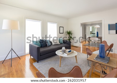 Decorated modern quaint living room interior with designer chairs, white round table, rug and couch.  - stock photo