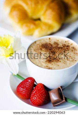 Decorated photo of cafe mocha, strawberries, chocolate, and croissant. - stock photo
