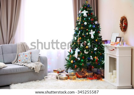 Decorated room with Christmas tree and presents under it - stock photo