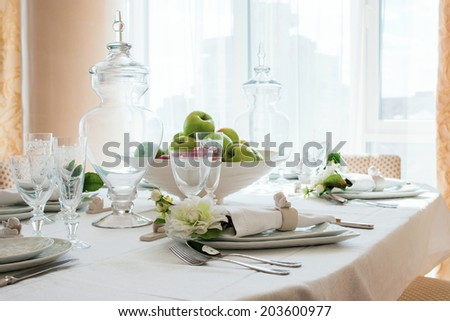 decorated table by the window in the dining room with apples - stock photo