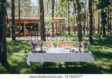 decorated table for the bride and groom standing on a green lawn in a pine forest - stock photo