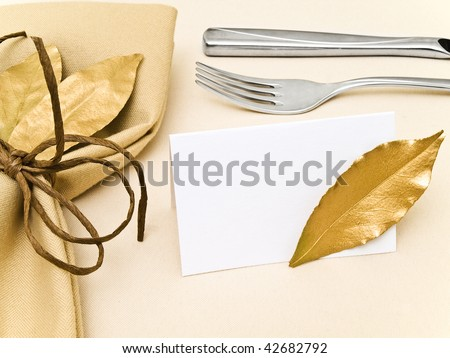 decorated table serving with golden bay leaves in serviette near knife, fork and guest card at beige - stock photo