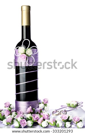 Decorated wedding bottle of champagne with roses, white pillow and two ring isolated on white background - stock photo