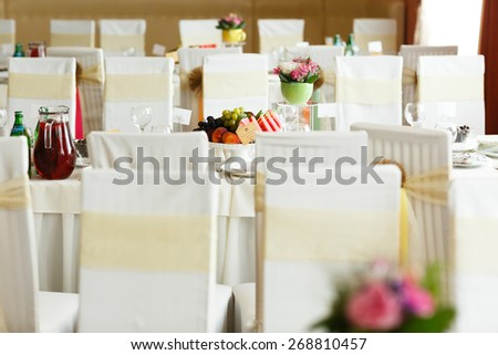 Decorated wedding restourant with white chairs and flowers - stock photo