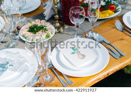 Decorated wedding table with candles in the garden. Appetizers on the table - stock photo