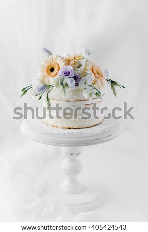 Decorated white naked cake rustic style for weddings, birthdays and events - stock photo