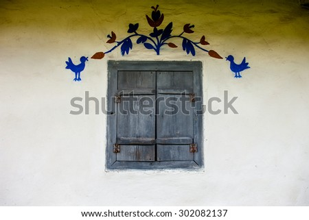 Decorated window with closed shutters of the old traditional Ukrainian house built in wattle and daub technique. - stock photo