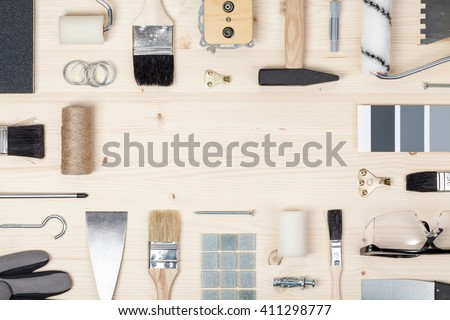 decorating and house renovation tools and accessories on wooden background. painter and decorator work table. flat lay frame composition with copy space top view - stock photo