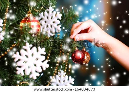Decorating Christmas tree on bright background - stock photo