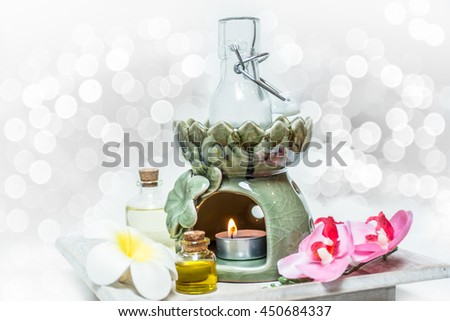 decoration of aroma essential oil with flower and candle on wooden background, spa concept. - stock photo