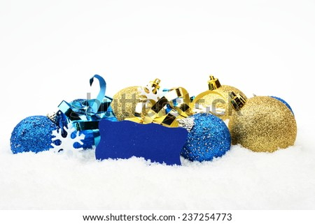 Decoration of blue and golden christmas baubles and gifts in line with wishes card on snow white background - stock photo