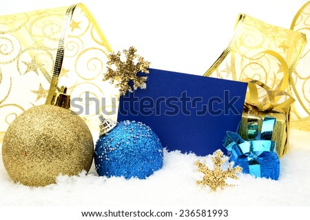 Decoration of golden and blue christmas baubles and gifts with ribbon with wishes card on snow white background - stock photo