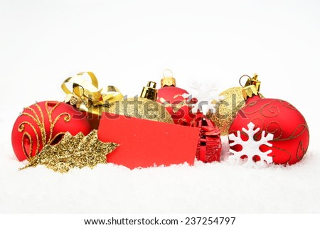 Decoration of golden,red christmas baubles and gifts with wishes card on snow isolated on white background - stock photo