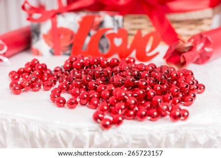 Decoration of red beads arranged on a white tablecloth with a red cutout of the word - Love - at a wedding reception - stock photo