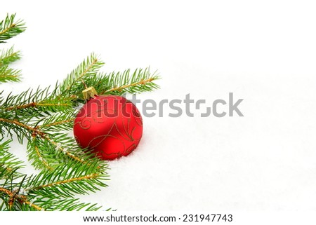Decoration of red christmas bauble on snow, christmas tree branch on white - stock photo