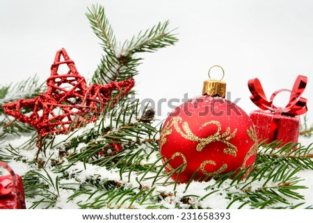 Decoration of red christmas gifts on snow with red star, christmas tree branch on white - stock photo