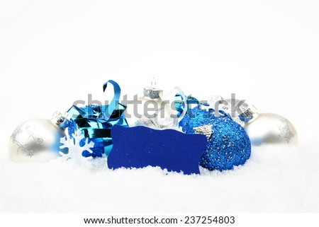 Decoration of silver and blue christmas baubles and gifts with wishes card on snow white background - stock photo