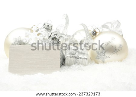 Decoration of silver christmas baubles and gifts in line with wishes card on snow white background - stock photo